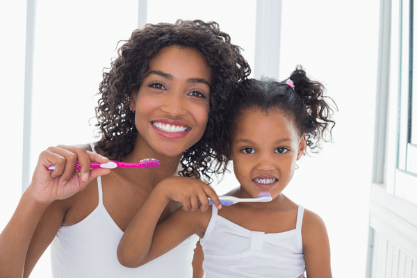 Mom and daughter smiling and brushing teeth American River Orthodontics Sacramento