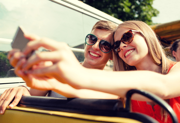 Young couple taking selfie outdoors while on tour