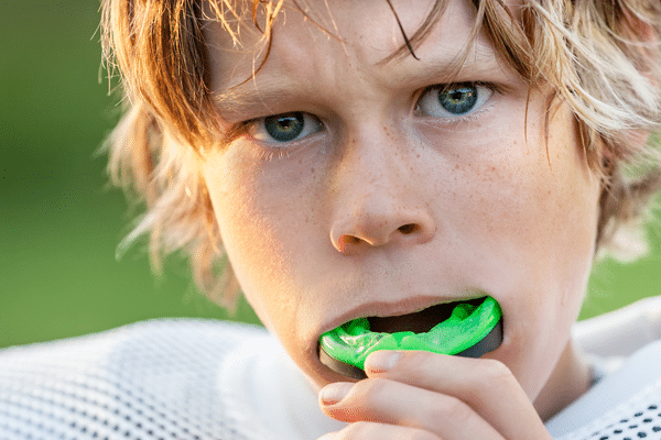 young football player inserting mouth guard