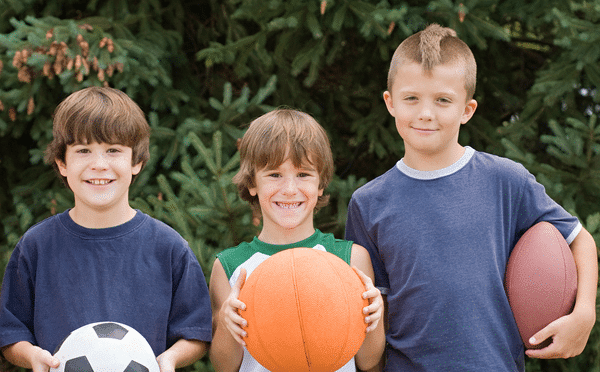 young boys holding sports balls
