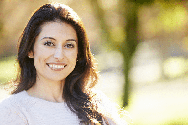 smiling woman outdoors wearing clear aligners in Roseville, CA