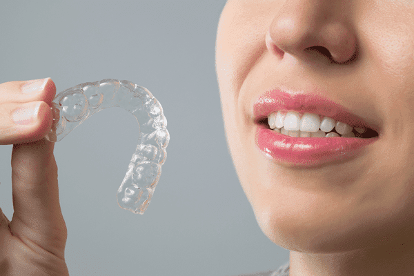 woman holding Invisalign clear aligner near Roseville, CA