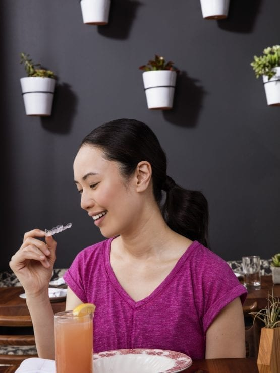 Woman holding aligner in cafe Invisalign