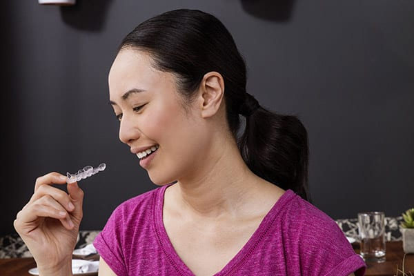 Woman holding clear aligner in cafe Invisalign