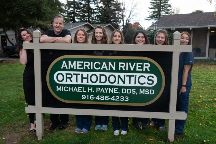 American River Orthodontics team outside next to sign