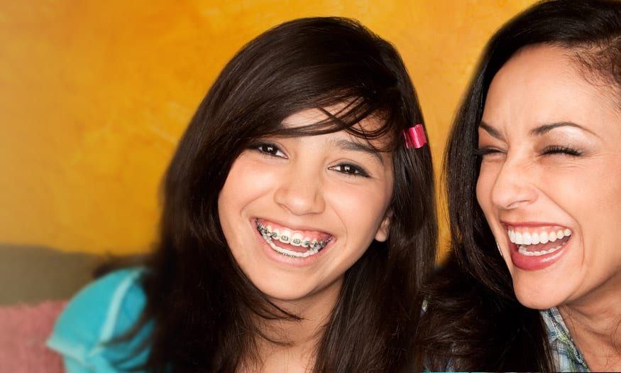 young girl wearing braces and smiling with her mother in sacramento, ca