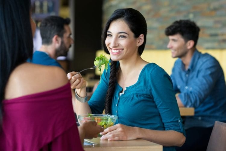 Woman eating salad in a restaurant with her friend
