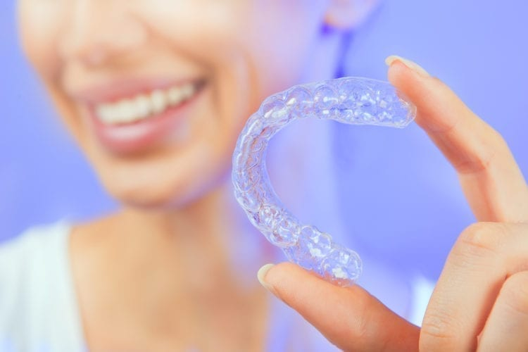 Closeup of woman holding a clear aligner, Sacramento, CA