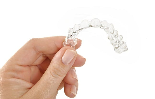 close up of hand holding a clear aligner